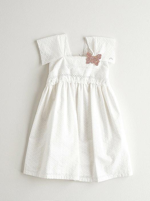 Vestido crudo niña Nanos con detalle pin mariposa en la pechera y manga sisa con puntilla